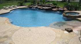 Freeform Pool and Spa with Raised Rock Wall and Custom Tanning Ledge